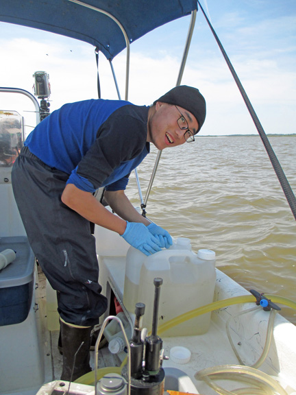 Researcher Lixin Zhu filters larger-volume surface water samples collected from the flow-through system to analyze for dissolved organic carbon.