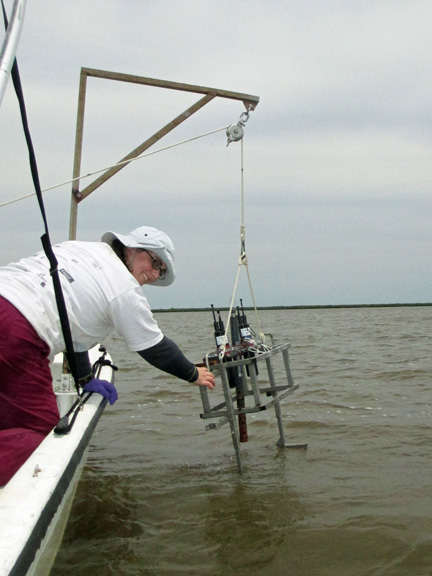 Researcher Kate Doyle lowers a sensor package into the water to measure salinity, temperature and depth.