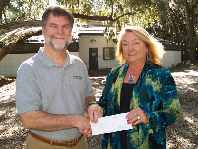 Michelle Vine presents her gift to UGA Skidaway Institute interim director Clark Alexander in front of the soon-to-be-renovated show barn